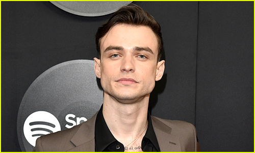 Thomas Doherty wears a brown jacket at an event