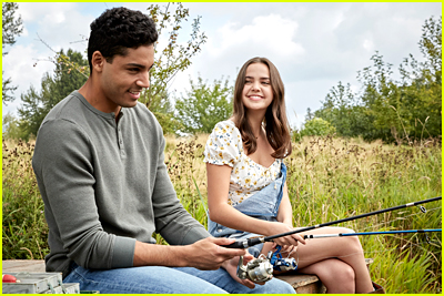 Michael Evans Behling and Bailee Madison sit in a field in 'A Cinderella Story: Starstruck'