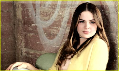 Chiara Aurelia leans against a wall while looking at the camera