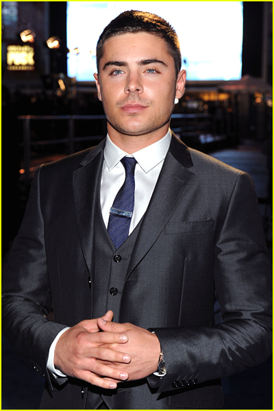 Zac Efron has really short hair and crosses his hands