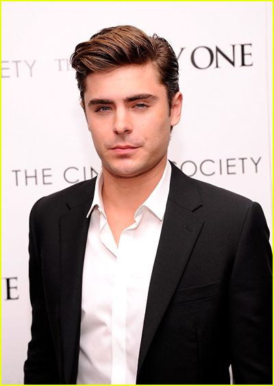 Zac Efron looks sauve in a black blazer and white shirt in front of a white backdrop