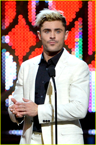 Zac Efron has blonde hair and wears a white suit jacket on stage at an awards show