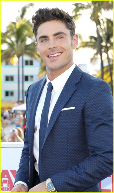 Zac Efron smiles in a suit at an outdoor event